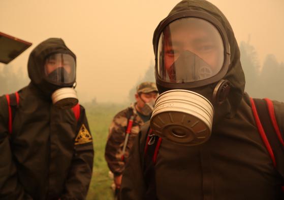 방독면을 쓰고 산불 진압 작업에 나선 러시아 야쿠티아 지역 소방관들. [로이터=연합뉴스]
