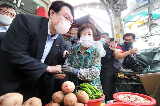 윤석열 전 검찰총장(왼쪽)이 20일 대구시 중구 서문시장을 찾아 상인과 대화하고 있다. 뉴스1