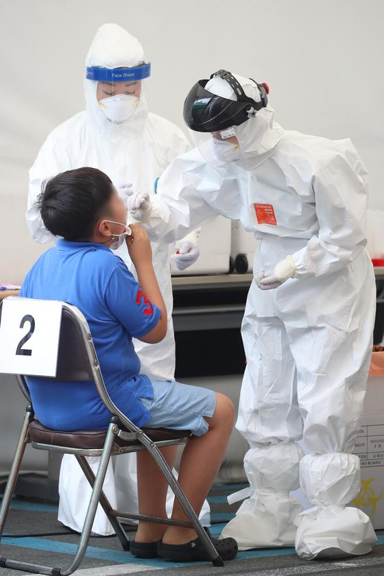 19일 오후 대구 수성구보건소에 마련된 선별진료소에서 의료진이 무더위와 싸우며 신종 코로나바이러스 감염증(코로나19) 진단검사를 위해 방문한 시민의 검체채취를 이어가고 있다. 뉴스1