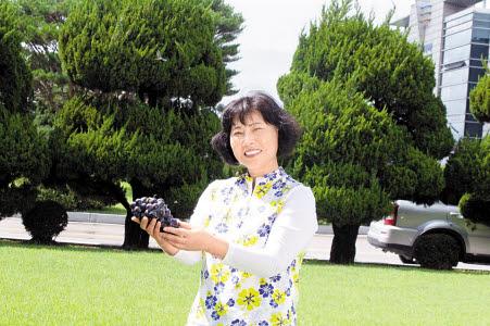 이경순 팜그린하우스 대표가 스마트팜 기술을 통해 키워 수확한 포도를 들고 환하게 웃고 있다. [사진 팜그린하우스]