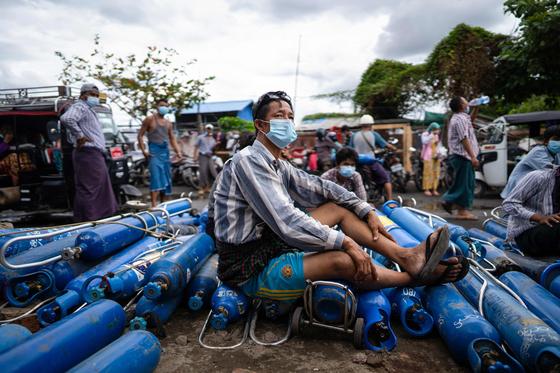지난 13일(현지시간) 미안먀 제2의 도시 만델레이 외곽의 한 산소공장에서 한 남성이 빈 산소통을 깔고 앉아있다.[AFP=연합뉴스]