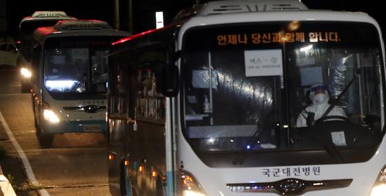 해외파병 임무 수행 중 코로나19 집단 감염이 발생한 청해부대 장병들을 태운 버스가 지난 20일 오후 충북 보은군 사회복무연수센터로 도착하고 있다. [뉴스1]