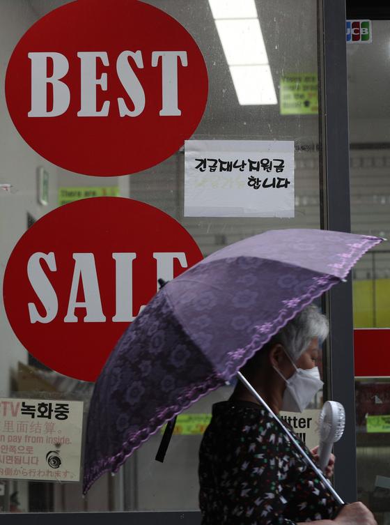 25일 서울 명동거리의 한 매장에 재난지원금 결제가 가능하다는 안내문이 붙어 있다. 뉴스1