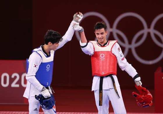 지난 25일 일본 지바 마쿠하리 메세 A홀에서 열린 2020 도쿄올림픽 태권도 남자 -68kg급 종목 16강전에서 우즈베키스탄의 울루그벡 라시토프 선수(오른쪽)가 자신에게 패배한 한국의 이대훈 선수(왼쪽)의 손을 들어주고 있다. 로이터=연합뉴스
