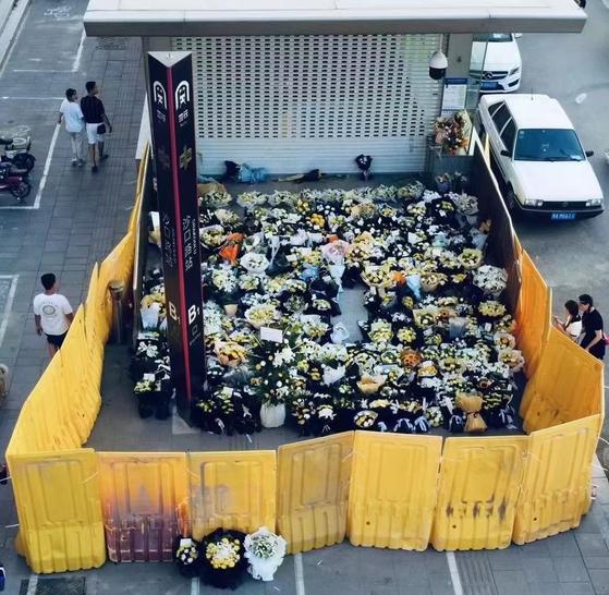 트위터의 파앤드니어(@YuanjinPhoto) 계정이 공개한 장저우(鄭州) 지하철 폭우 참사 현장의 '꽃 가림막'. [트위터 캡처]