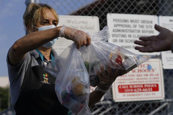 미국 캘리포니아주(州) 로스앤젤레스(LA)의 한 교사가 주정부가 제공하는 무료 급식을 나눠주고 있다.[AP=연합뉴스]