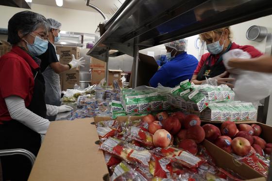 지난 15일 로스앤젤레스(LA)의 한 학교에서 급식 서비스 직원들이 주정부가 제공하는 무료 급식을 나눠주기 위해 음식을 포장하고 있다. [AP=연합뉴스]
