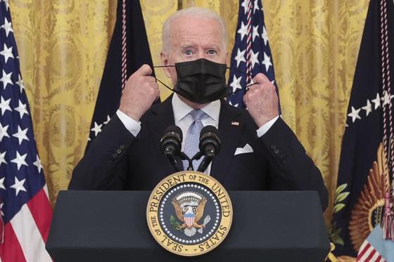 29일(현지시간) 조 바이든 미국 대통령이 백악관 브리핑 전까지 쓰고 있던 마스크를 벗고 있다. 이날 바이든 대통령은 미국인에게 다시 한번 백신 접종을 당부했다. [EPA=연합뉴스]