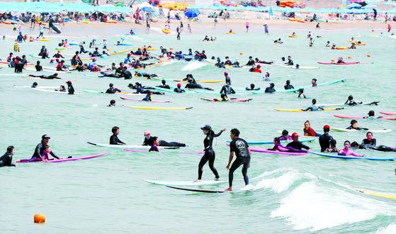 폭염이 이어진 지난달 30일 오후 부산 송정해수욕장을 찾은 서퍼들이 서핑을 즐기고 있다. [연합뉴스]