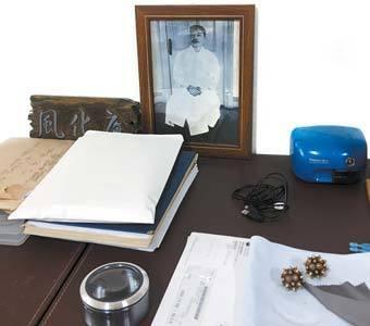 자료 선반에 놓인 '風化庵(풍화암)' 편액과 안중근 의사의 사진. 앞쪽에 큼직한 루페가 보인다.