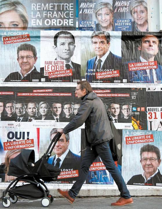 23일 치러지는 프랑스 대선 1차 투표를 앞두고 한 유권자가 유모차를 끌고 선거 벽보로 도배가 된 건물벽 앞을 지나고 있다. [파리 로이터=뉴스1]