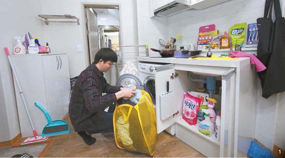 1 대학생 이호성(25)씨가 서울 성북구 삼선동 자취방에서 빨랫감을 세탁기에 넣고 있다. 빨래바구니 등 생필품 대부분은 다이소에서 구입한 것들이다. 김경빈 기자