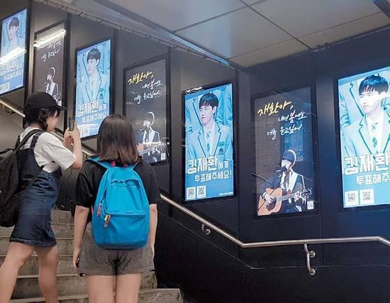 지하철 2호선 신촌역 출입구에 전시된 아이돌 연습생 광고 앞에서 팬들이 사진을 찍고 있다.