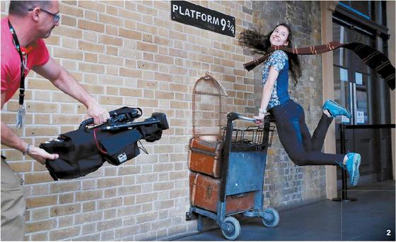 2 '해리 포터'가 20주년을 맞은 지난달 26일, 영국 런던 킹스크로스역의 '9와 4분의 3 승강장'에서 한 여성이 해리 포터 짐수레를 잡고 뛰어오르고 있다. [사진 워너브러더스코리아·로이터=연합]