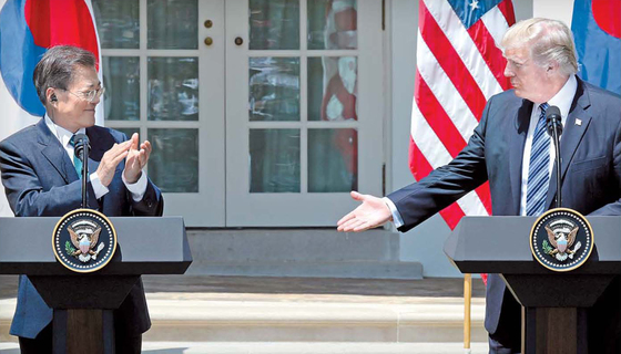 문재인 대통령이 지난달 30일(현지시간) 백악관에서 공동 언론발표를 마친 뒤 박수를 치자 도널드 트럼프 미국 대통령이 악수를 청하고 있다. 김성룡 기자
