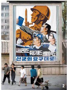 2 2006년 10월 3일 북한의 첫 핵 실험 다음날의 평양 거리 모습. '사상과 투쟁, 생활도 선군의 요구대로'라는 선전구호판 아래로 평양시민들이 지나가고 있다. [중앙포토?조선중앙통신=연합뉴스]
