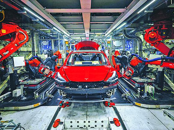 머스크 테슬라 CEO 는 완전 자동화 공장에서 인간이 아닌 로봇으로 전기차를 만들어낼 계획을 세웠다. 하지만 그의 실험은 실패로 끝났다. 로봇이 빠르고 정확하게 자동차를 만들지 못하면서 생산 차질과 많은 제품 하자가 발생했다. 사진은 로봇이 모델3를 조립하는 프리몬트 공장 모습. [사진 블룸버그]
