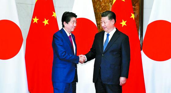 2012년 취임 후 처음으로 중국을 공식 방문한 아베 신조 일본 총리가 26일 베이징 댜오위타이에서 열린 정상회담에 앞서 시진핑 중국 국가주석과 악수하고 있다. [AP=연합뉴스]