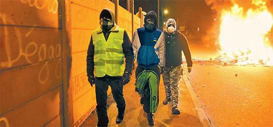 노란조끼 시위대가 지난 11일(현지시간) 프랑스 북부 도시 르망에서 '마크롱은 사임하라'는 문구가 쓰여있는 벽 앞을 지나고 있다. [AFP=연합뉴스]