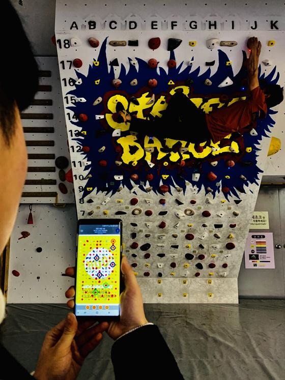 서울 성산동의 홍대클라이밍에서 '문보드' 앱을 통해 실내암벽을 즐기는 클라이머. 앱에서 등반 문제를 선택하면 클라이밍 월의 LED가 반짝이고(사진상의 초록색, 파란색, 붉은색) 클라이머는 이 LED를 따라 등반하게 된다. 김홍준 기자