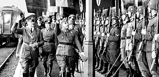 1940년 10월 프랑스 앙다예(2차대전 중 독일 점령)역 플랫폼 열병식. 나치 독일의 히틀러(왼쪽)와 스페인의 프랑코가 독일 의장대에 파시스트식 답례를 하고 있다. 작은 역의 좁은 플랫폼 탓에 붉은 카펫은 프랑코의 발걸음이 차지했다. 왼편은 프랑코가 타고 온 열차. 앙다예 국경 너머는 스페인 이룬. [중앙포토]