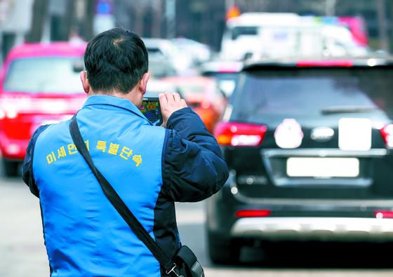 미세먼지 비상저감조치가 발령된 22일 서울 세종로사거리 부근에서 서울시 차량공해저감과 직원이 공회전 차량을 단속하고 있다. [연합뉴스]