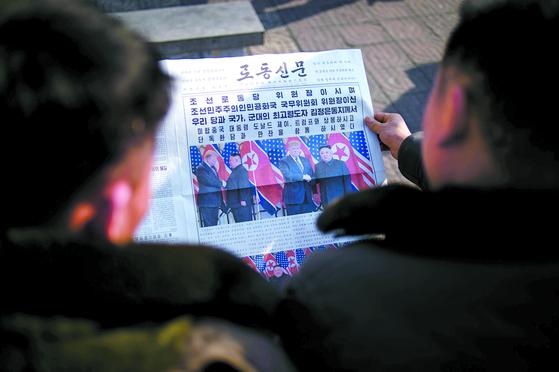 지난달 28일 김일성광장에 나온 평양 시민들이 베트남 하노이에서 열린 도널드 트럼프 미국 대통령과 김정은 북한 국무위원장의 제2차 정상회담 소식을 보도한 노동신문을 읽고 있다. [AFP=연합뉴스]