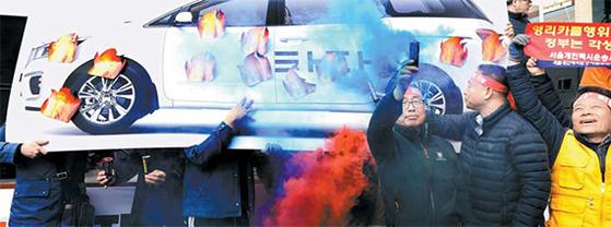 21일 서울 광화문광장에서 열린 고 임정남씨 추모 집회에서 서울 개인택시 운전사들이 승차공유 서비스 '타다' 추방을 요구하며 화형식 퍼포먼스를 벌이고 있다. [뉴시스]