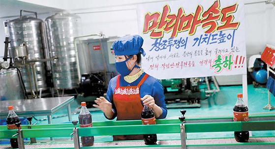 지난 13일 평양의 한 식품공장 근로자가 컨베이어벨트 앞에서 작업하고 있다. 생산을 독려하는 현수막이 눈에 띈다. [AP=연합뉴스]