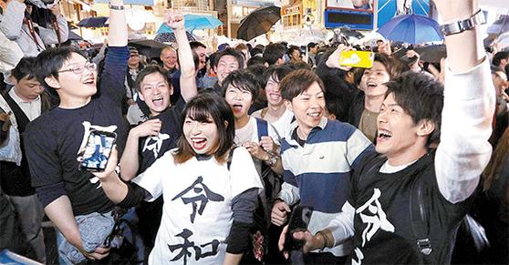 아키히토 전 일왕이 퇴위하고 나루히토 새 일왕이 즉위한 지난 1일 일본 오사카 시내에서 젊은이들이 새 연호인 '레이와(令和)'가 적힌 옷을 입고 레이와 시대의 개막을 축하하고 있다. [지지통신]