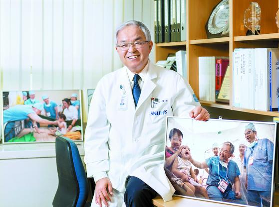 백롱민 원장이 베트남 의료 봉사 현장 사진을 들고 환하게 웃고 있다. 그는 30년 간 안면기형 어린이를 무료로 수술해 왔다. [김동하 객원기자]