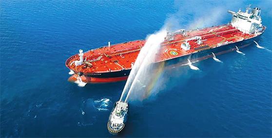 이란 해군 소속 선박이 지난 13일 오만해에서 공격을 받아 불이 난 유조선에 접근해 진화 작업을 벌이고 있다. [AP=뉴시스]