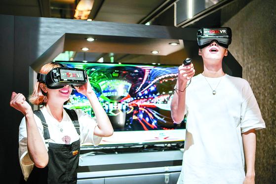 서울 종로구 LoL파크 내에 설치된 SKT 5GX 체험존에서 모델들이 VR 현장 생중계 서비스를 체험하고 있다. [뉴스1]