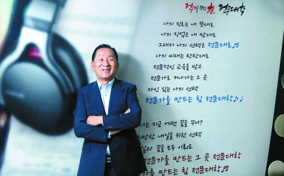 이기우 한국전문대학교협의회 회장이 전문가를 만드는 힘을 주제로 한 '전문대학 브랜드 송'이 적힌 포스터 앞에서 포즈를 취하고 있다. 김경빈 기자