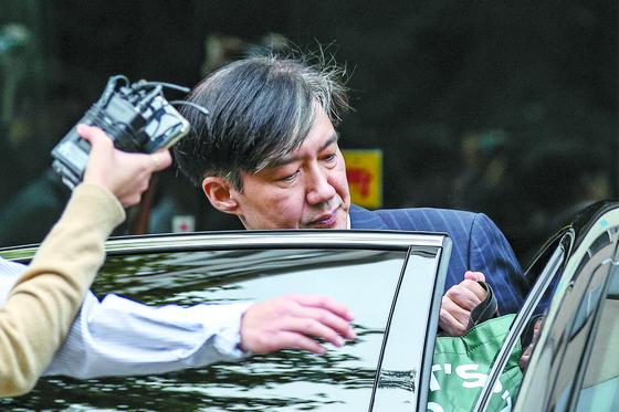 """자택 압수수색 검사와 통화해 논란이 일고 있는 조국 법무부 장관이 27일 오전 서울 방배동 자택 앞에서 승용차에 오르고 있다. 조 장관은 이날 보도된 한 주간지 인터뷰에서 '이를 악물고 출근하고 있다"""" '언제 어디까지일지 모르지만 갈 수 있는 데까지 가볼 생각""""이라고 밝혔다. [뉴스1]"""