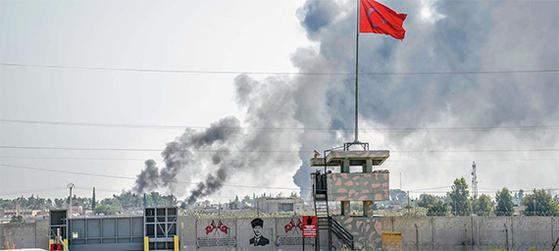 지난 10일(현지시간) 터키군의 공격을 받은 시리아 국경 도시 탈 아비아드에서 시커먼 연기가 피어오르고 있다. 터키군은 이날 장벽 너머 시리아 지역에 박격포 공격을 했다. [AFP=연합뉴스]