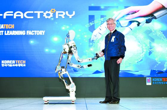 이성기 한국기술교육대 총장이 '스마트 러닝 팩토리'에서 사람처럼 움직일 수 있는 유연한 로봇팔 '엠비덱스 '와 반갑게 악수하고 있다. 이 로봇팔은 산학협력으로 개발했으며 지난해 미국 전기전자기술협회가 주관하는 국제로봇 학술대회에서 우승을 차지했다. 김성태 객원기자
