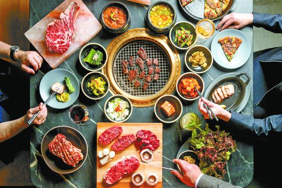 개점 4개월 만에 미쉐린 1스타를 받은 뉴욕의 한국식 고깃집 '꽃'의 상차림. 부위별 고기와 쌈야채와 찌개를 같이 차려내고 직원이 옆에서 직접 고기를 구워주는 한국식 스타일을 도입했다. [사진 꽃, 게리 허]