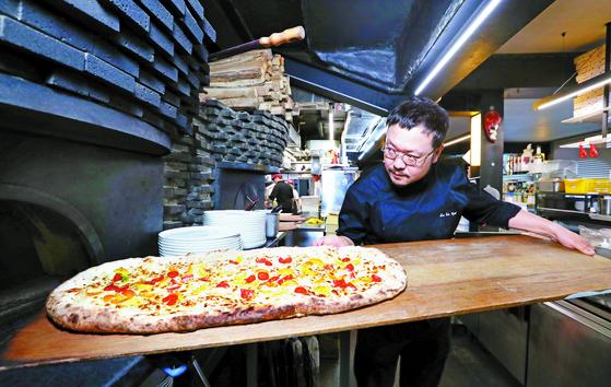 이진형 총괄 셰프가 제 17회 로마 피자 월드컵 메트로·팔라 부문 중 팔라에 도전해 만든 피자는 크기가 폭 30㎝, 길이는 70㎝에 이르는 대형 피자다. 1차로 구워진 피자 위에 훈제 연어, 루케타(야생 루콜라) 등 2차 토핑을 더해 완성한다. 신인섭 기자