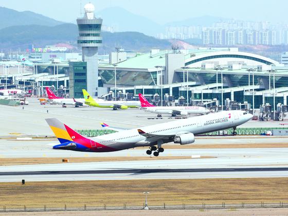 인천국제공항에서 이륙하는 아시아나항공 여객기와 대기 중인 LCC 항공기들. [연합뉴스]