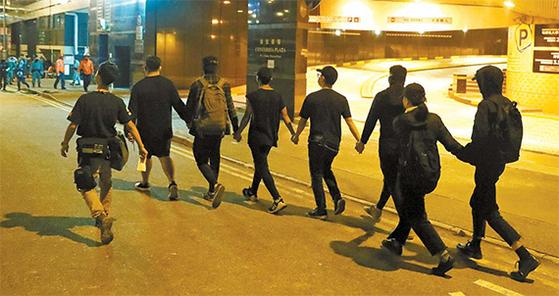 21일 홍콩이공대를 점거한 반정부 시위대가 경찰에 투항을 하고 있다. 이공대 사태가 사실상 끝나자 시위대 세력이 크게 위축됐다. [로이터=연합뉴스]