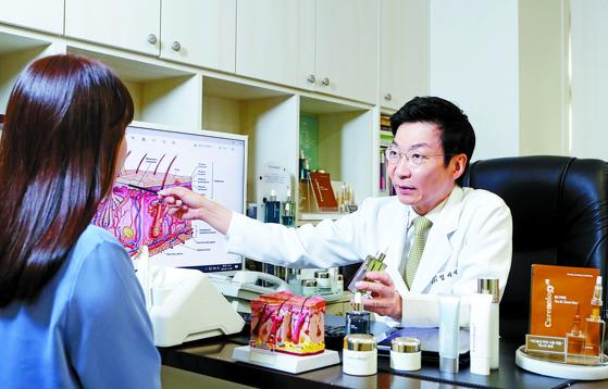 임이석 원장이 환자를 진료하고 있다. 그는 환자의 피부 관리 고민을 덜기 위해 안전한 화장품을 연구·개발해 내놓기도 했다. 신인섭 기자