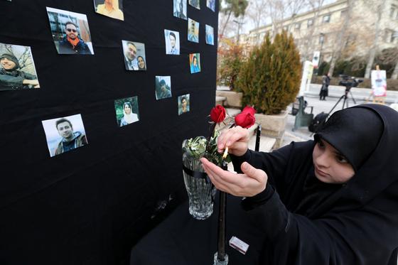 이란의 한 여학생이 14일 우크라이나 민항기 희생자를 추모하며 초에 불을 붙이고 있다. [AFP=연합뉴스]