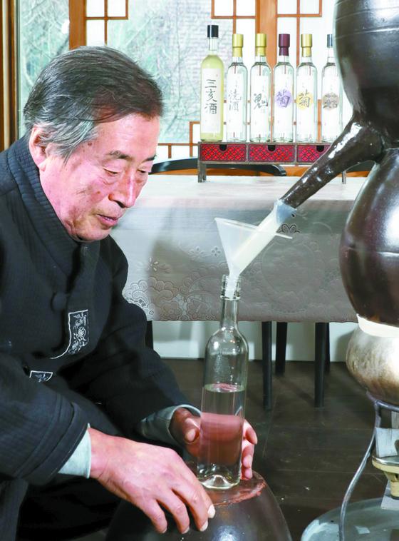 은 3560g으로 만든 솥에 소줏고리를 걸고 전통방식으로 내린 삼해소주를 병에 받는 김택상 명인. 김경빈 기자
