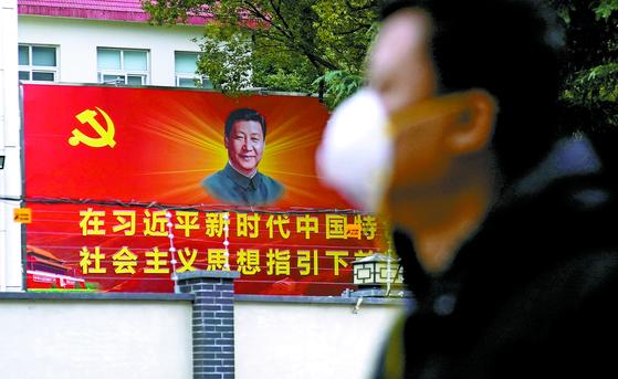 지난 10일 중국 상하이에서 한 시민이 마스크를 착용한 채 시진핑 국가주석의 얼굴이 그려진 간판을 지나고 있다. [로이터=연합뉴스]