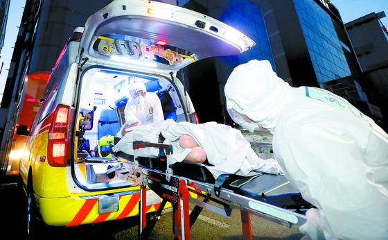 지난 18일 환자와 직원 등 75명의 코로나19 확진자가 발생한 대구 한사랑요양병원에서 구급대원들이 환자를 이송하고 있다. [대구=뉴시스]