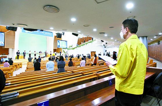 지난 22일 대전 의 한 교회에서 시청 공무원이 코로나19 확산 방지를 위한 '예배 참석자 간 2m 이상 거리 두기' 규정을 점검하고 있다. [연합뉴스]