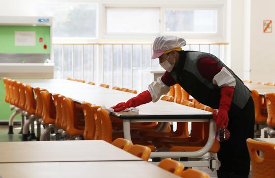 지난달 18일 서울의 한 초등학교 급식실에서 관계자가 식탁을 닦고 있다. [연합뉴스]