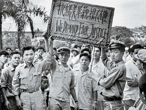 """1957년 5월 24일 오후. '미군의 인권 경시를 항의한다""""는 팻말을 들고 미 대사관 앞에서 시위하는 청궁(成功)고중 학생들. 청궁고중은 장징궈가 설립한 청년구국단의 중심기지였다. 오른쪽 첫째가 훗날 대 작가로 명성을 떨친 천잉쩐(陳映眞). [사진 김명호]"""