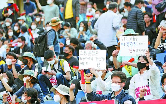 노동절인 지난 1일 오후 서울 세종대로 세종문화회관 계단에서 열린 코로나19 비정규직 긴급행동 기자회견에서 참석자들이 손 피켓을 들고 있다. [뉴스1]